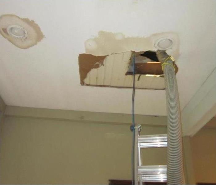 A cut out in the water damaged ceiling with a later underneath the cut out