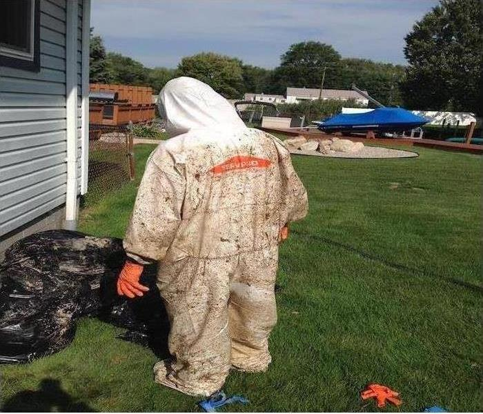 SERVPRO team member in a PPE suit, restoring a damaged home.
