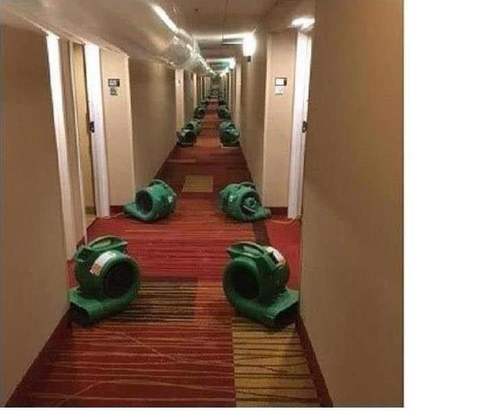 Hotel hallway with SERVPRO equipment drying out rooms