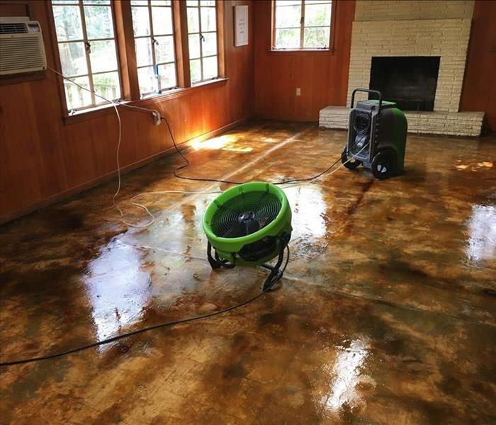 An empty room that has water on the floor with SERVPRO's equipment drying it up